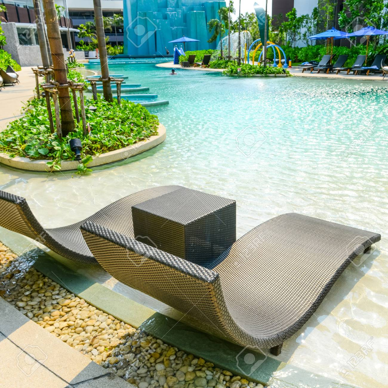 Beach chairs in luxury swimming pool at tropical hotel resort,..