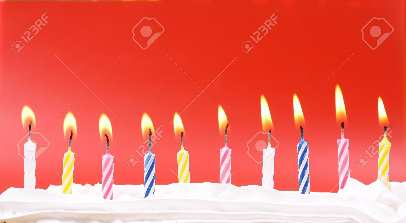 10 lit birthday candles in bright colors with red background stock