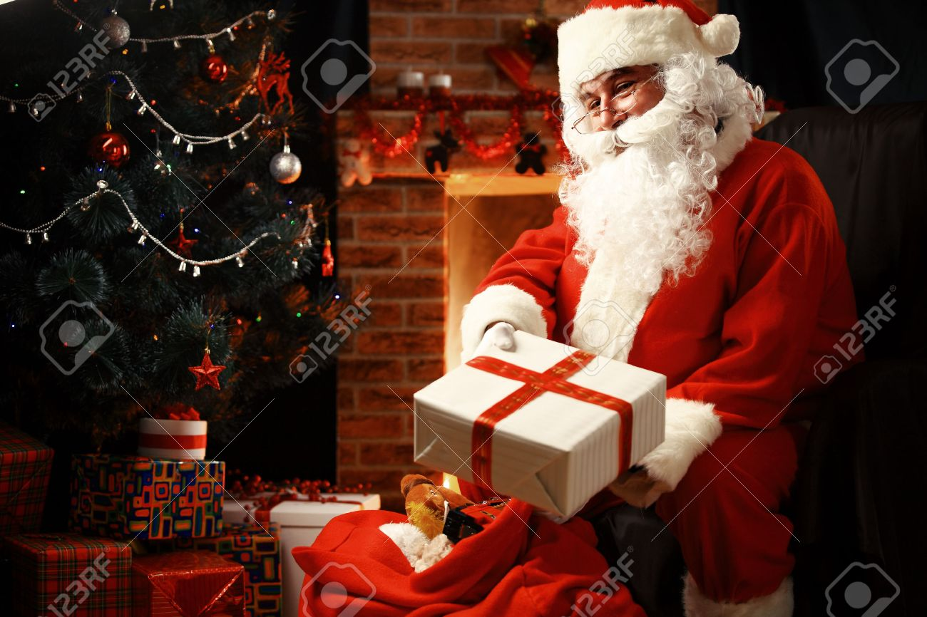 Santa Claus brought gifts for Christmas and having a rest by the fireplace. Home decoration. - 46918200