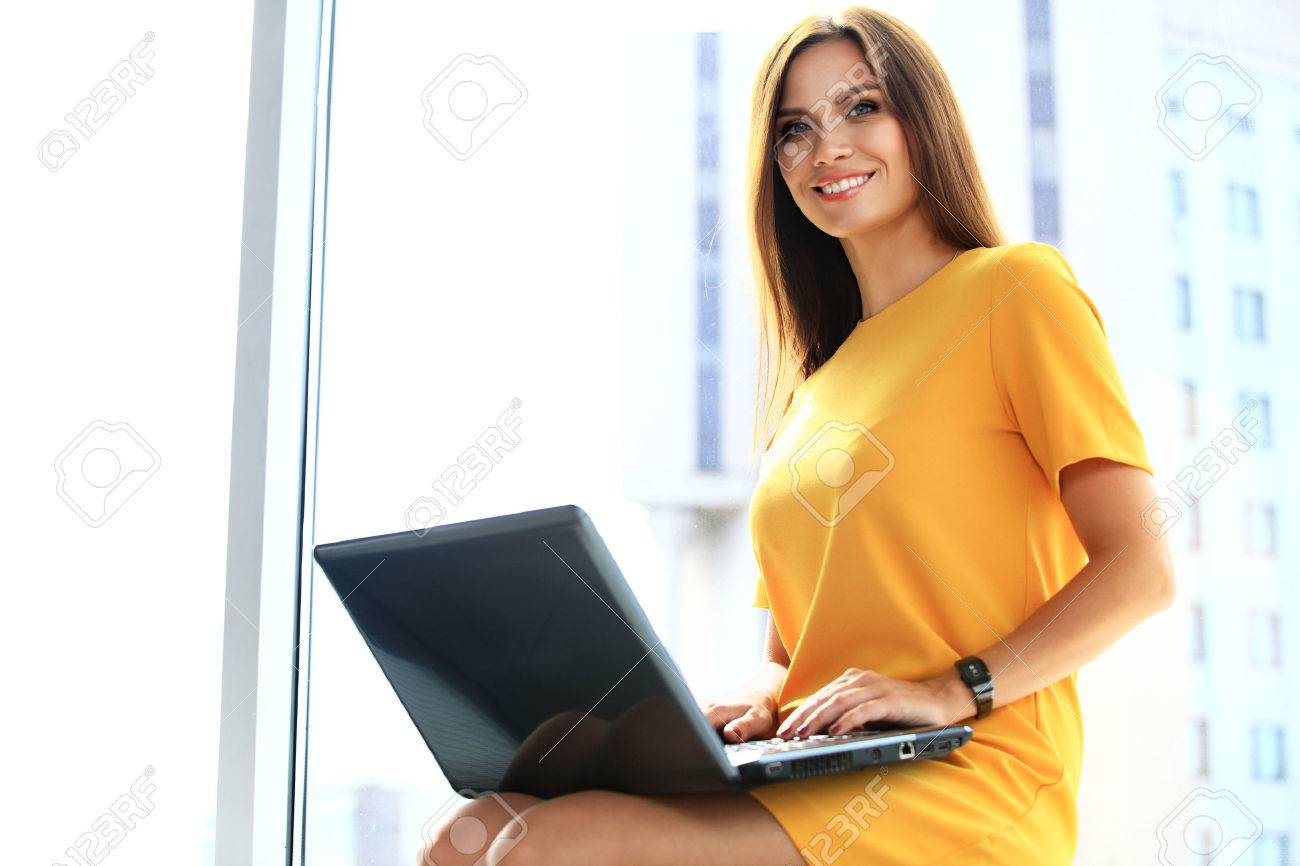 Portrait of a young business woman using laptop at office - 48284619