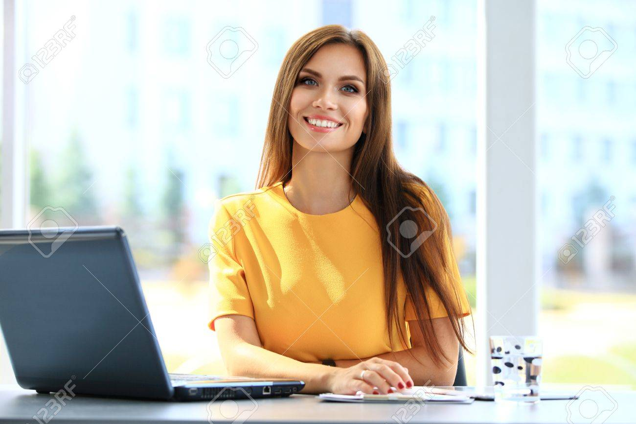 Portrait of a young business woman using laptop at office - 48284661