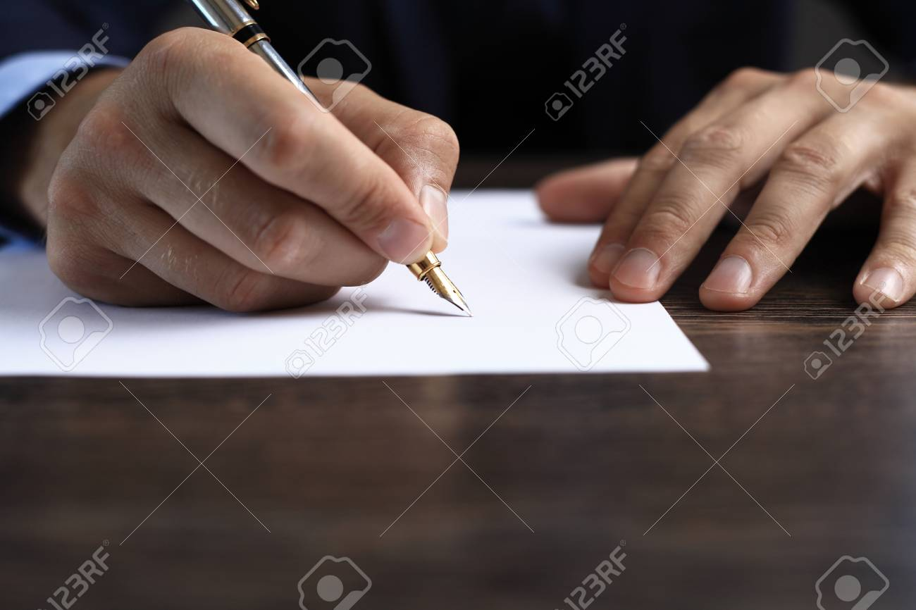 Man signing a document or writing correspondence with a close up view of his hand with the pen and sheet of notepaper on a desk top. - 50162864