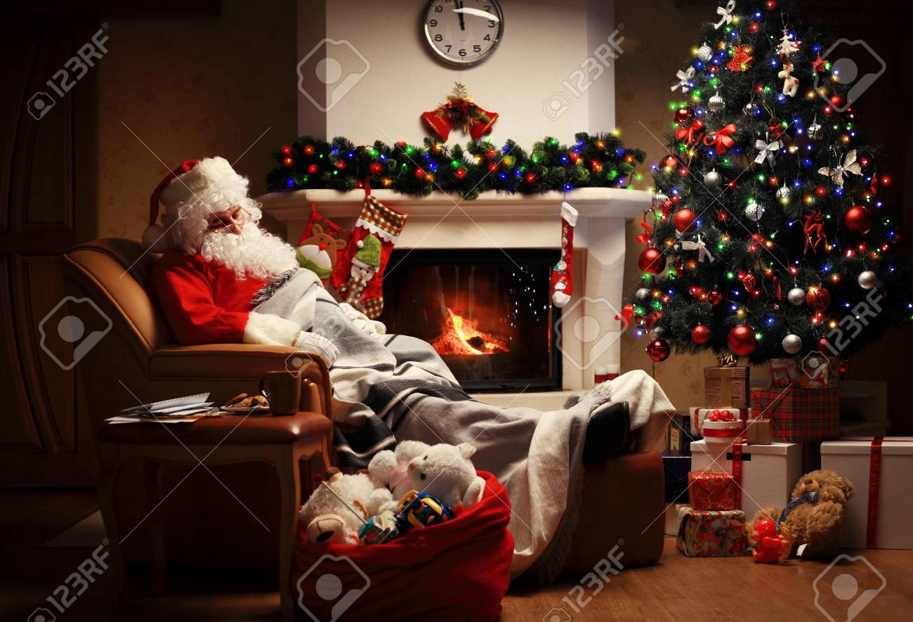 Santa Claus having a rest in a comfortable chair near the fireplace at home. - 65005873