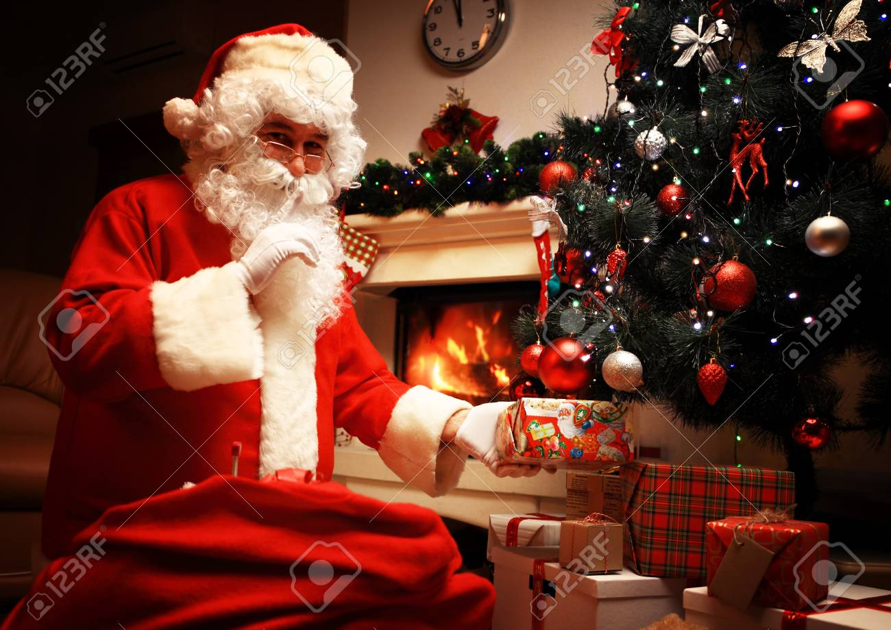 Santa Claus Putting Gift Box Or Present Under Christmas Tree Stock Photo Picture And Royalty Free Image Image 65857247
