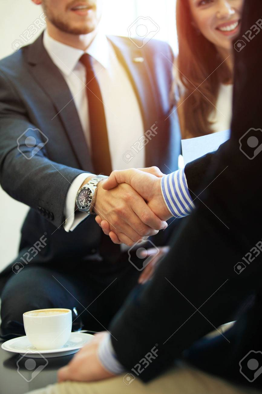 Business people shaking hands, finishing up a meeting. - 68418219