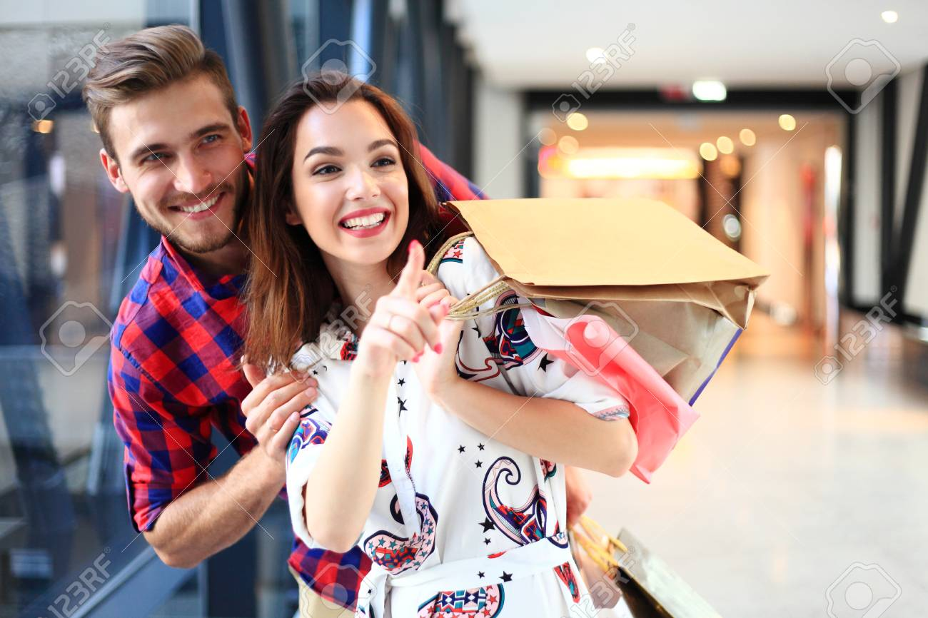 sale, consumerism and people concept - happy young couple with shopping bags walking in mall. - 94878214