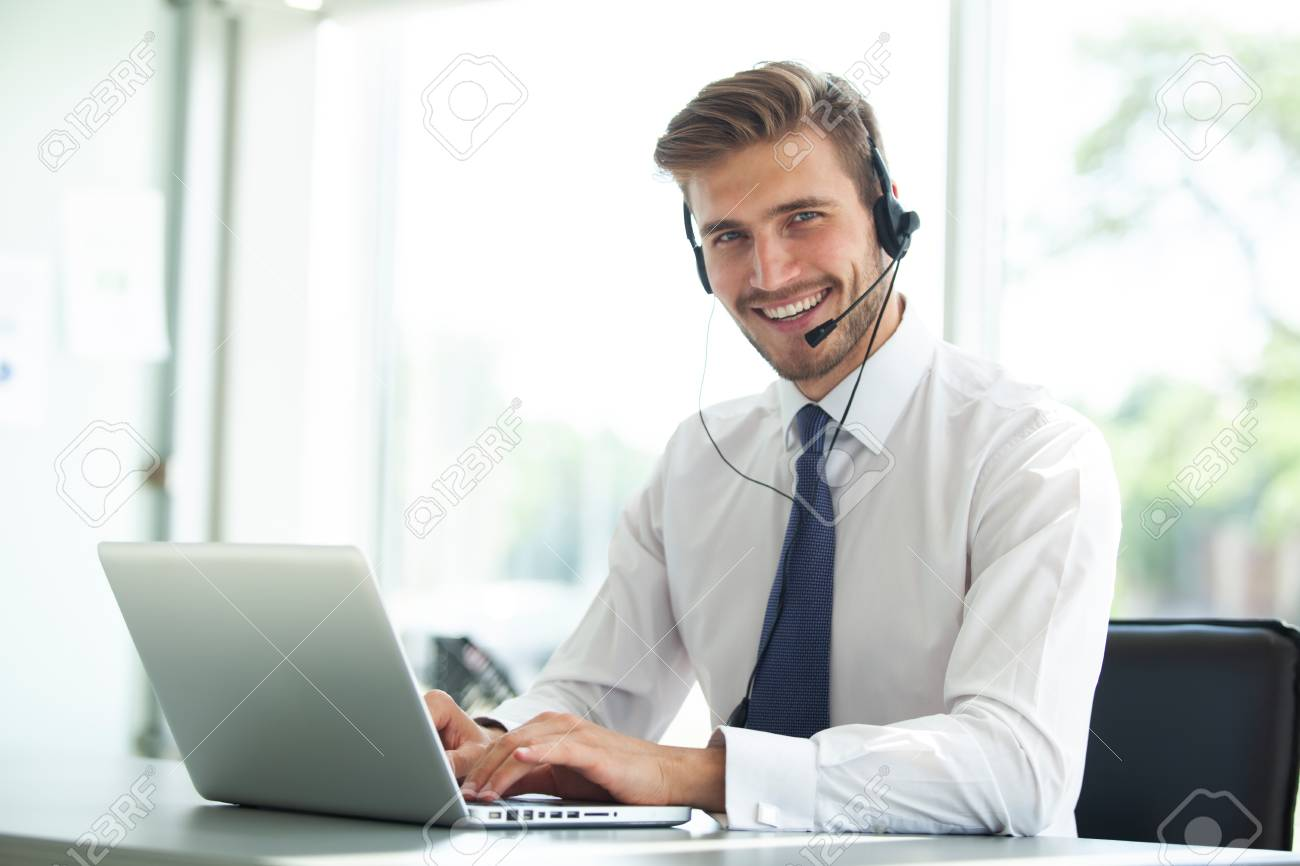 Happy young male customer support executive working in office. - 106720489