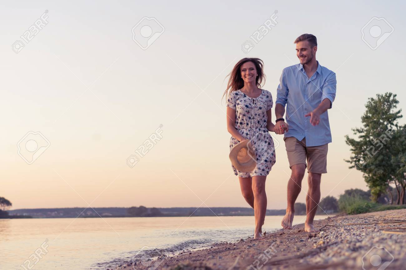 couple walking on the beach at sunset ロイヤリティーフリーフォト