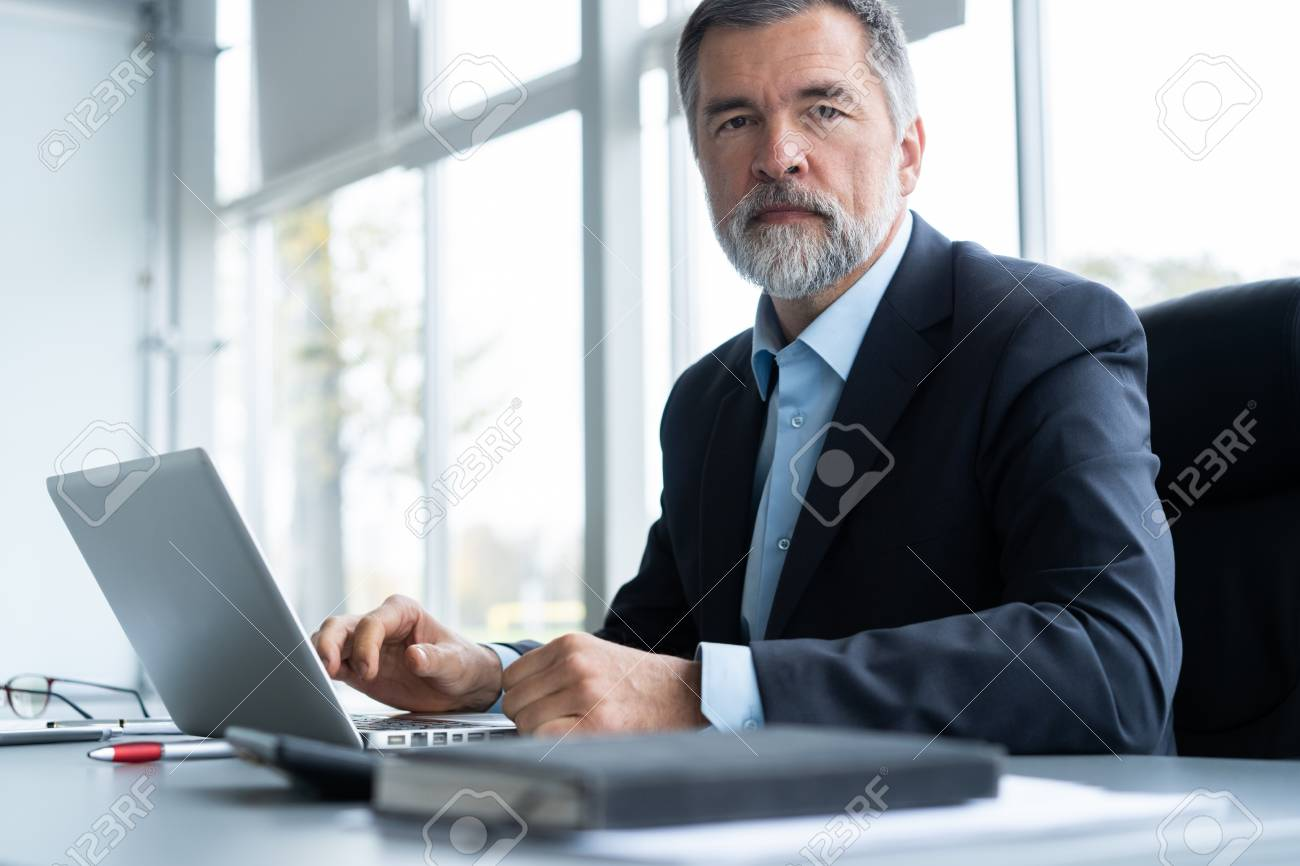 Senior businessman working on laptop computer in the office. - 113386546