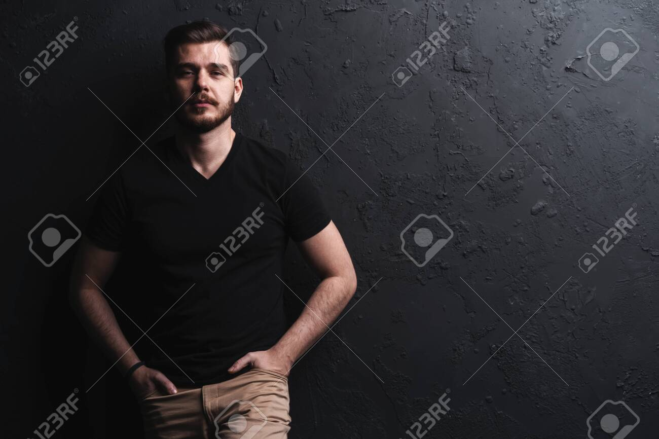 young fashion man posing for the camera on black background - 115439592