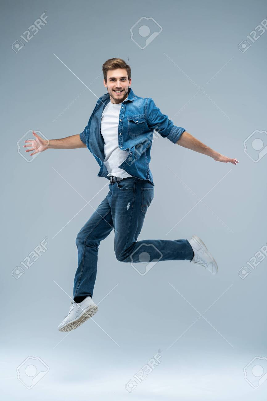Full length portrait of a happy excited beardedman jumping and looking at camera isolated over grey background. - 116347241