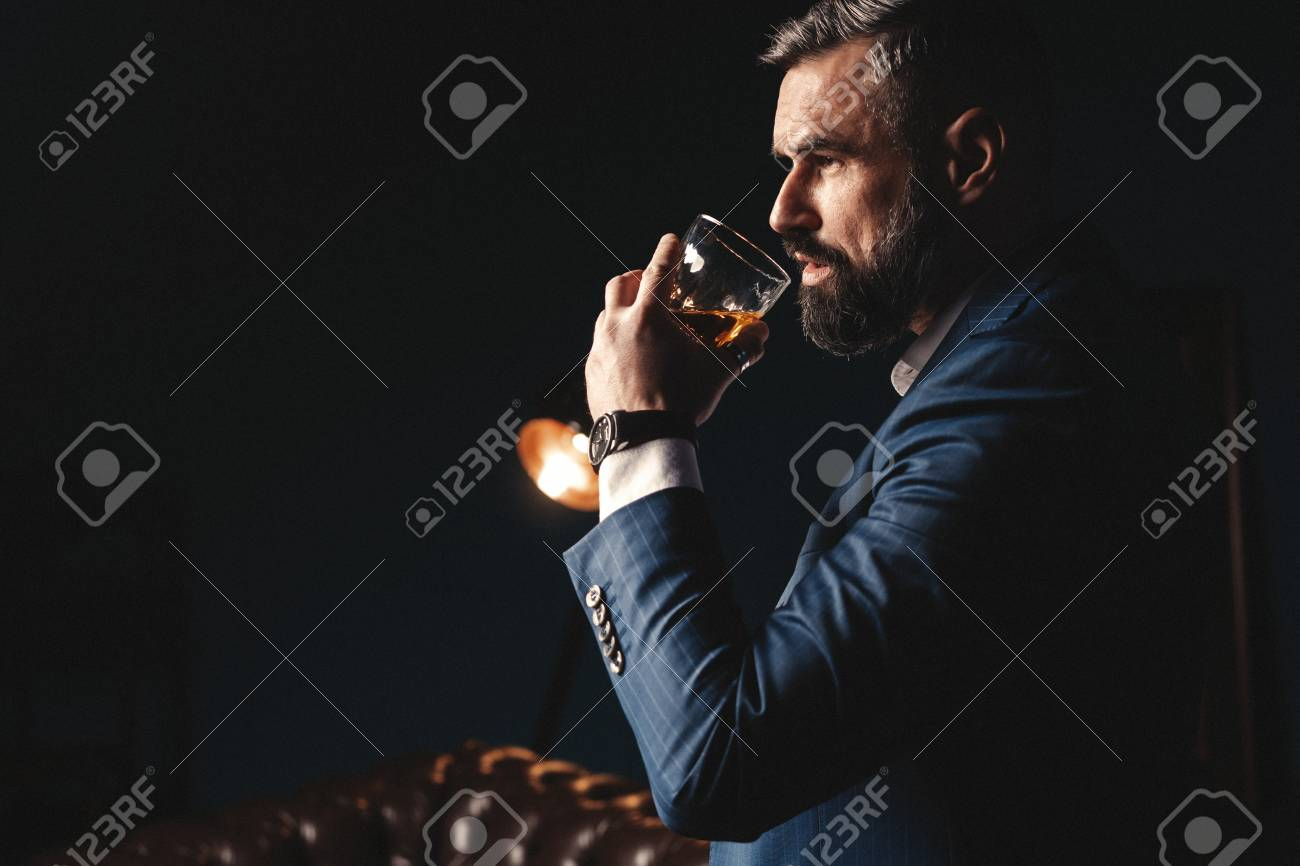 Degustation, tasting. Man with beard holds glass of brandy. Tasting and degustation concept. Bearded businessman in elegant suit with glass of whiskey - 117091809