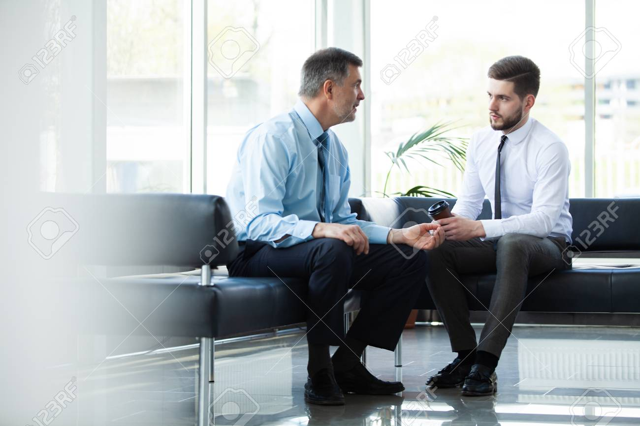 Mature businessman using a digital tablet to discuss information with a younger colleague in a modern business lounge. - 117097432
