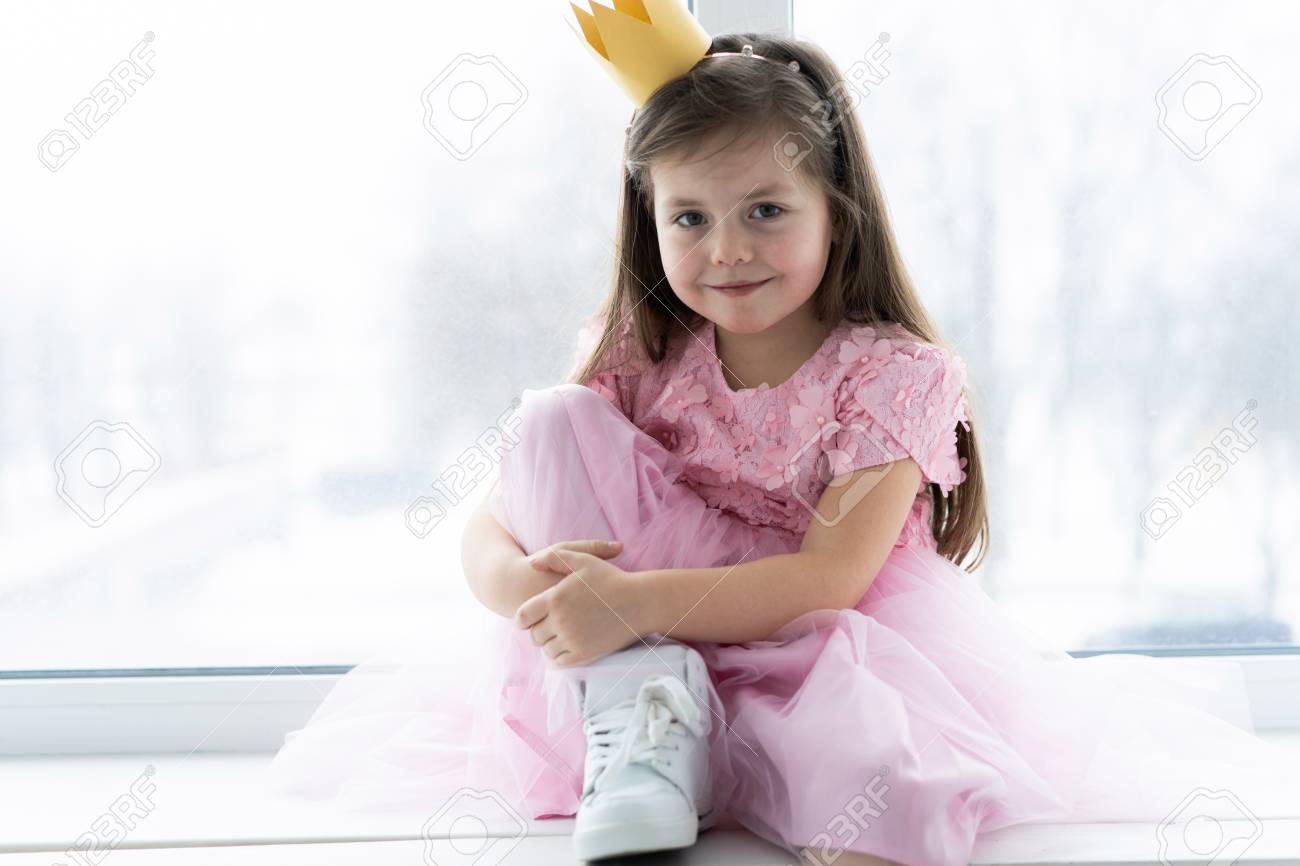 Cute little girl in a princess costume. Pretty child preparing for a costume party. Beautiful queen in gold crown. - 117980184