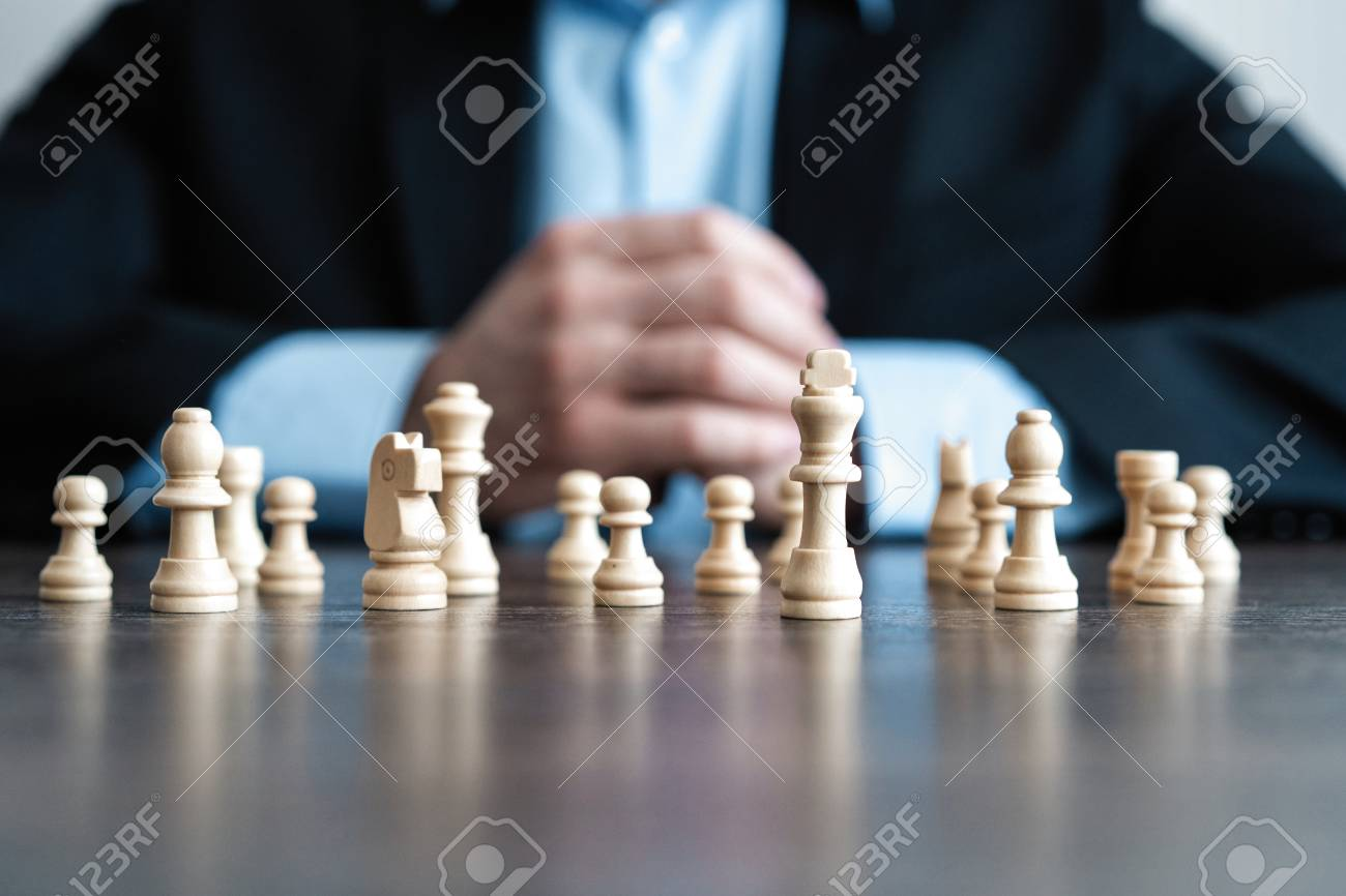 Businessman with clasped hands planning strategy with chess figures on table. Strategy, leadership and teamwork concept. - 119770100