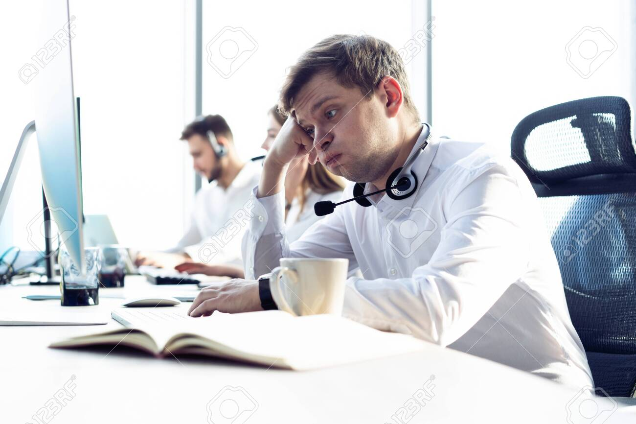Worried or tired business man with headset working on computer in office. - 121990777