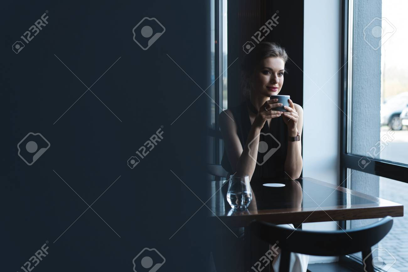 Portrait of gorgeous female drinking tea or coffee and looking with smile out of the coffee shop window while enjoying her leisure time - 124623163