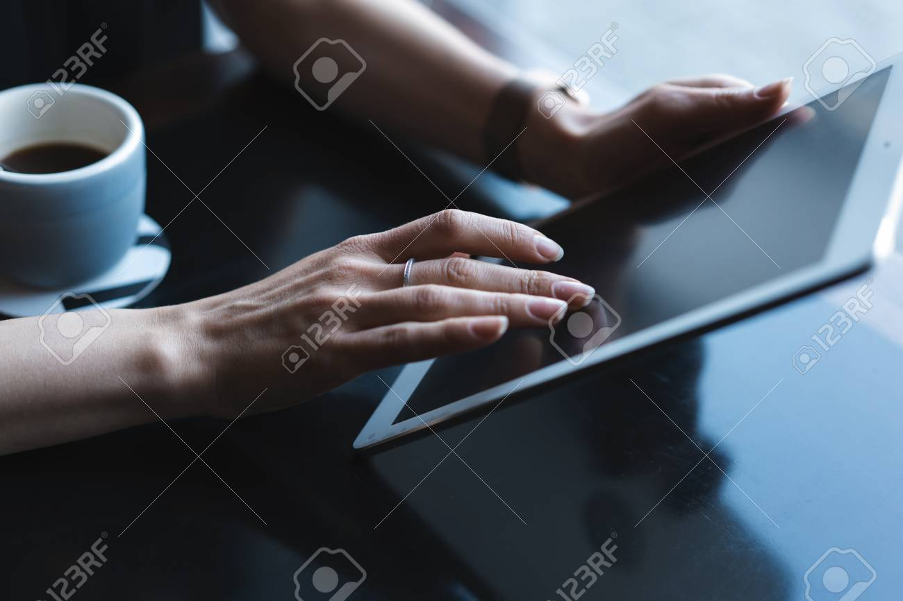 Close up of hands woman using her tablet pc in restaurant,cafe - 124623370