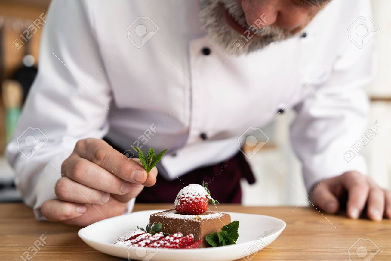 Close up pastry chef decoration delicious dessert dish, serving for customers in bakery, garnishing dessert plate in commercial kitchen. - 124623584