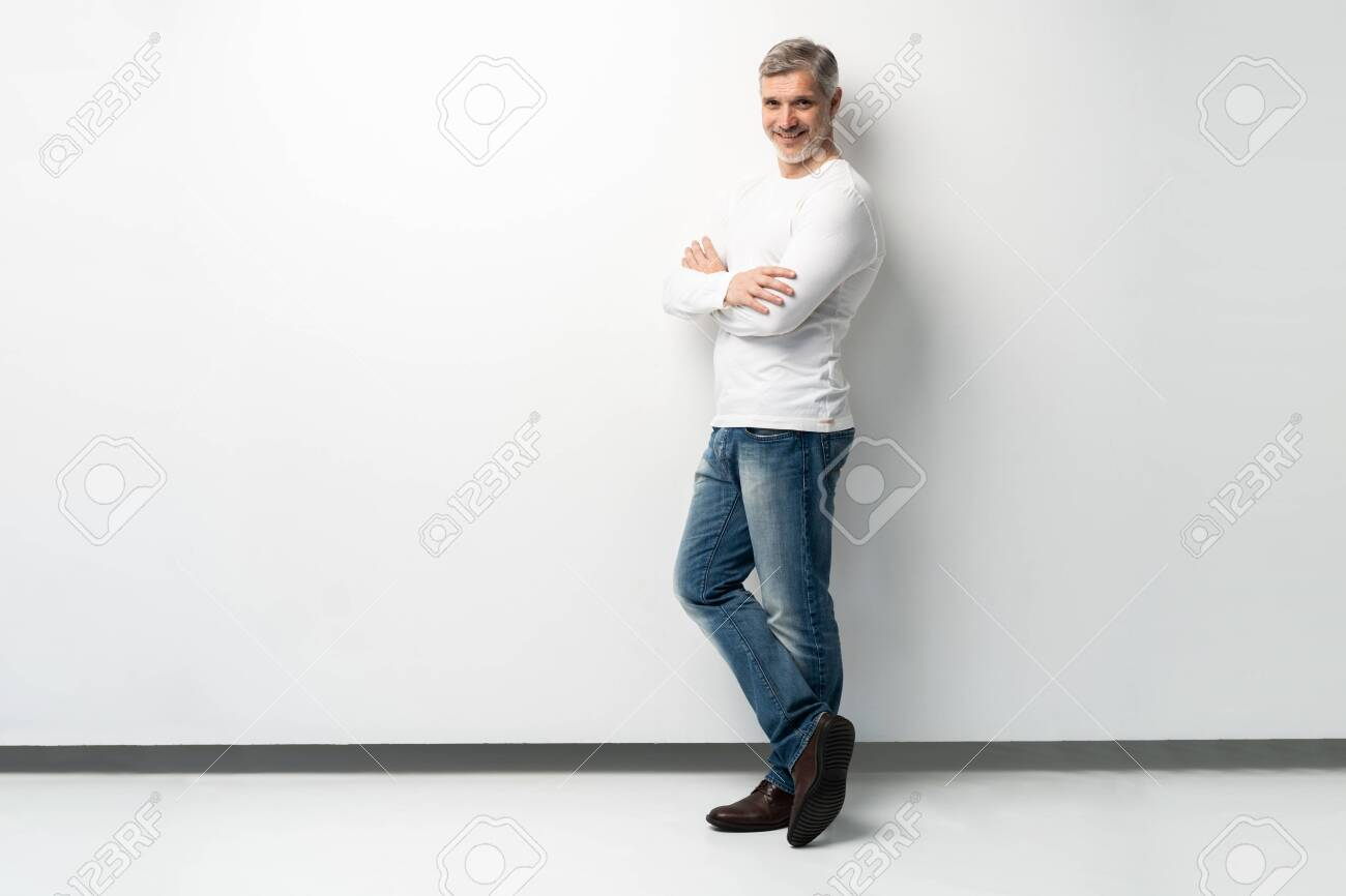Full body portrait of relaxed mature man standing with arms crossed over white background. - 123587276