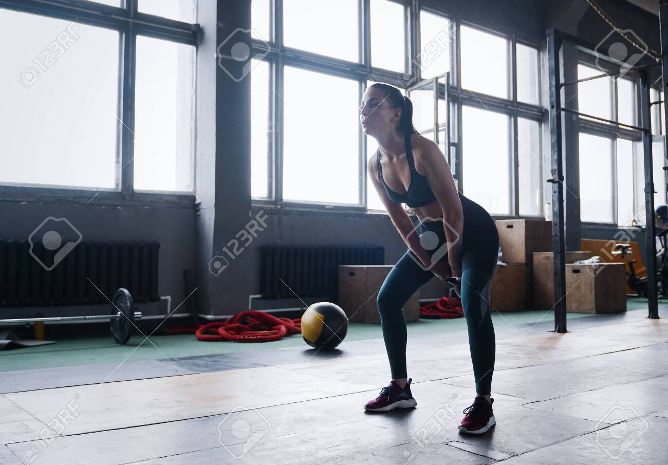 Young fitness female exercise with kettle bell. Caucasian woman doing crossfit workout at gym. - 128291933