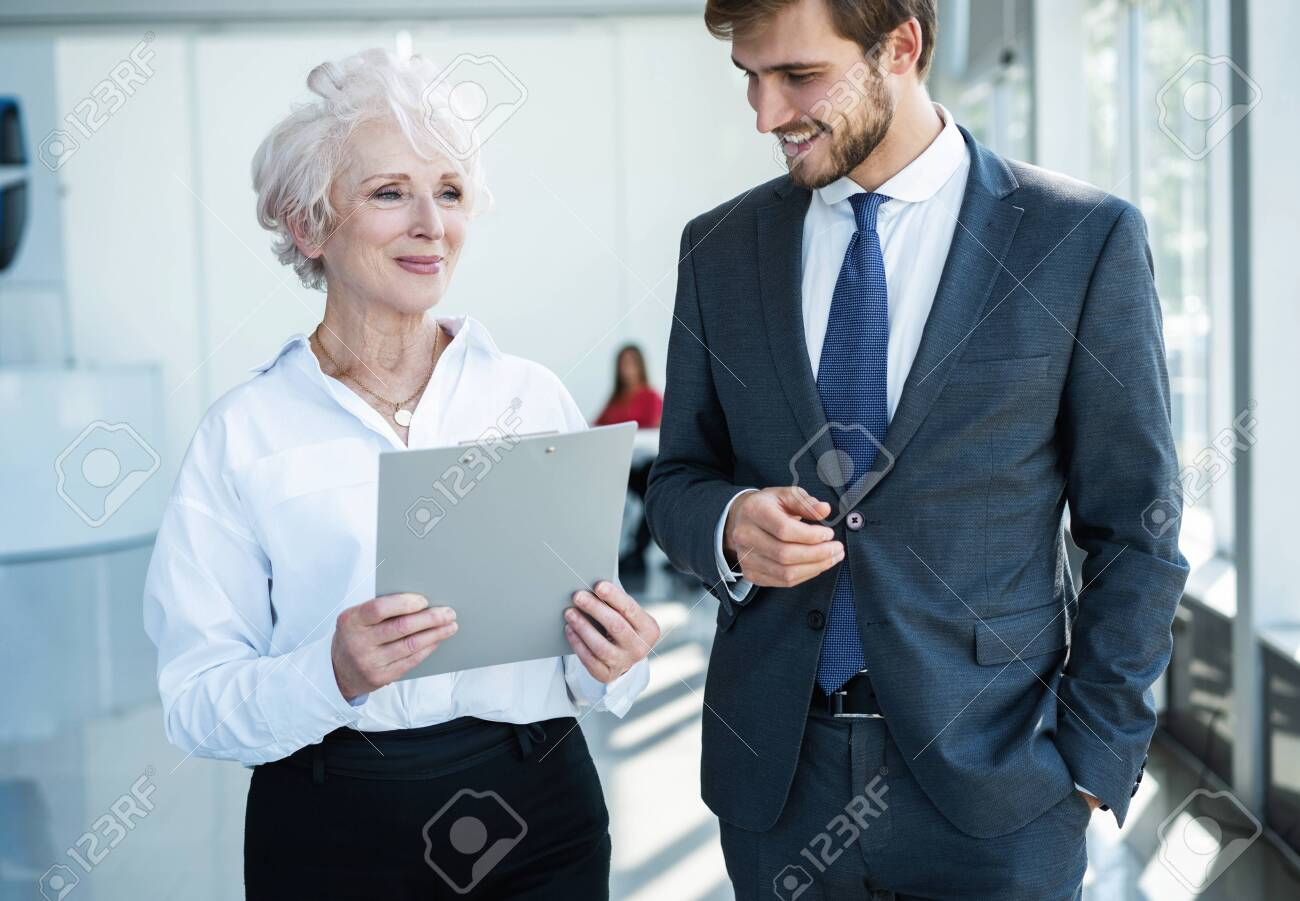 Senior mature caucasian female executive ceo discuss report with young colleague - 131810620