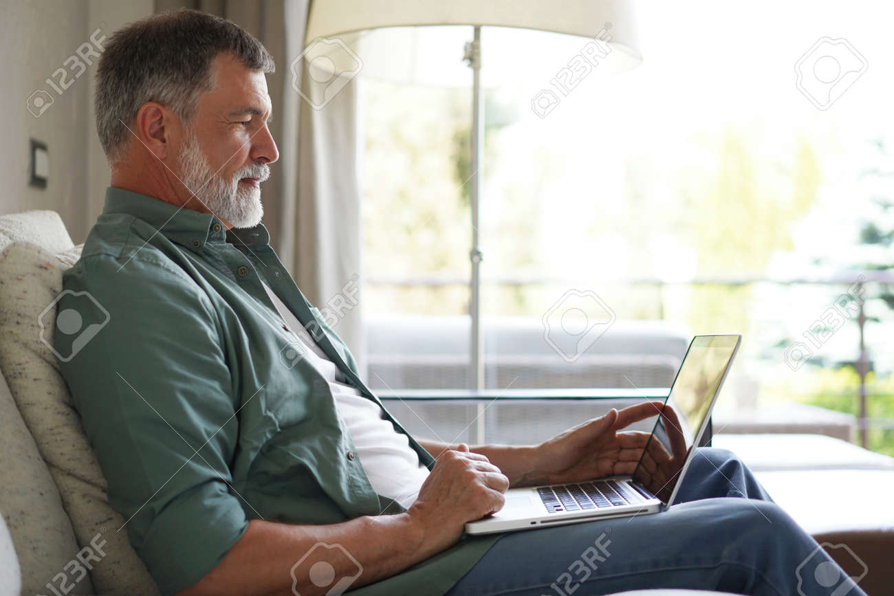 Portrait of happy mature man in casual clothes using laptop lying on sofa in house. - 171563191