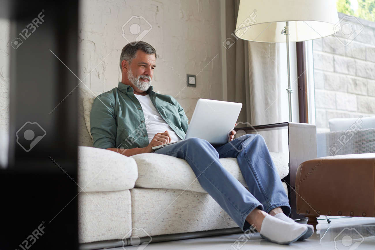 Portrait of happy mature man in casual clothes using laptop lying on sofa in house. - 171563456