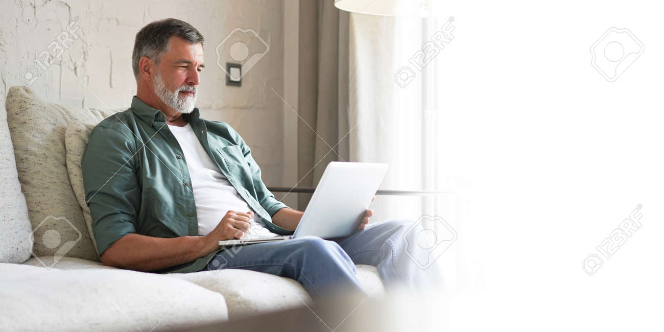 Portrait of happy mature man in casual clothes using laptop lying on sofa in house. - 171563178
