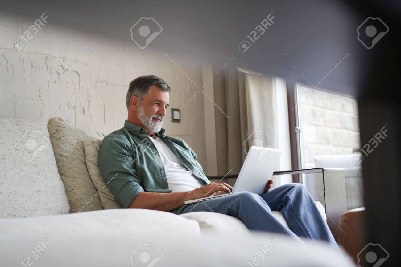 Portrait of happy mature man in casual clothes using laptop lying on sofa in house. - 171563268