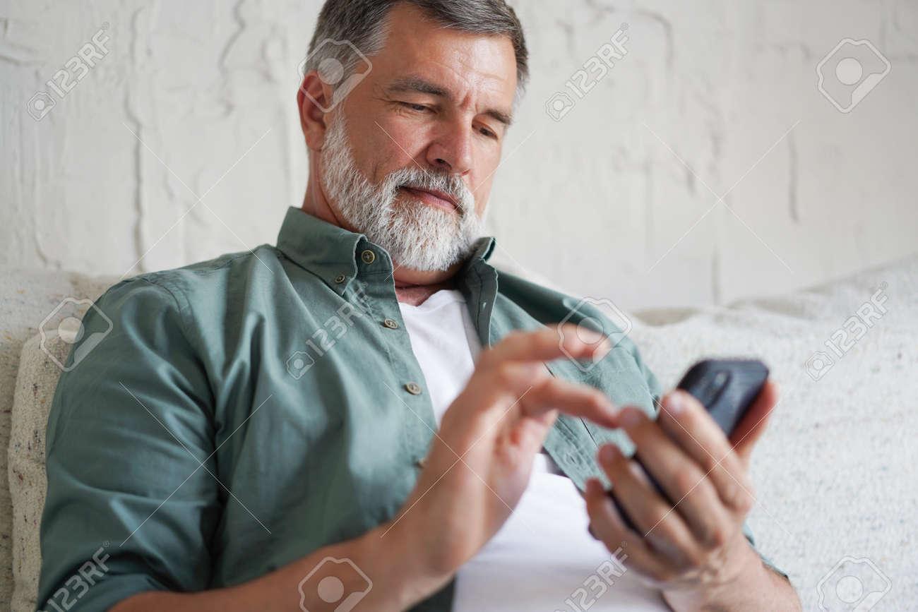 Smiling Senior Man Using Cellphone Browsing Internet Sitting On Sofa Indoor. - 171566580