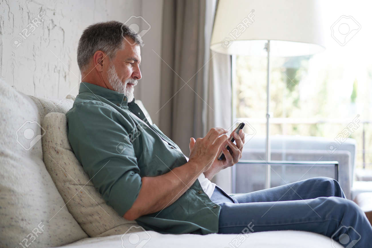 Smiling Senior Man Using Cellphone Browsing Internet Sitting On Sofa Indoor. - 171566653