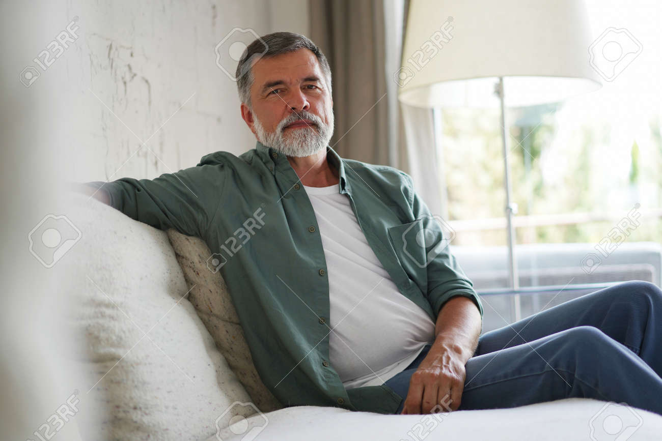 Portrait of attractive senior man sitting in sofa at home. - 171566677