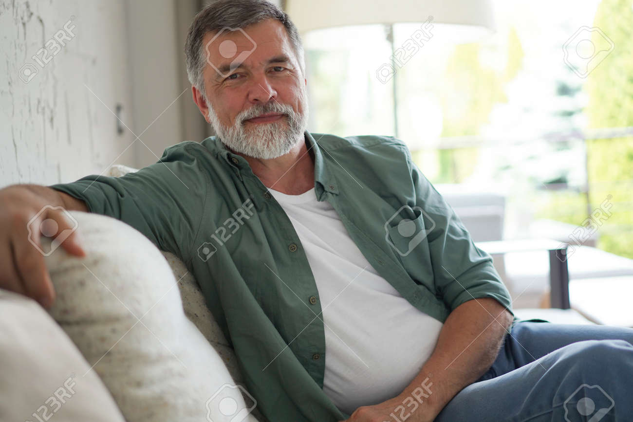 Portrait of attractive senior man sitting in sofa at home. - 171566710