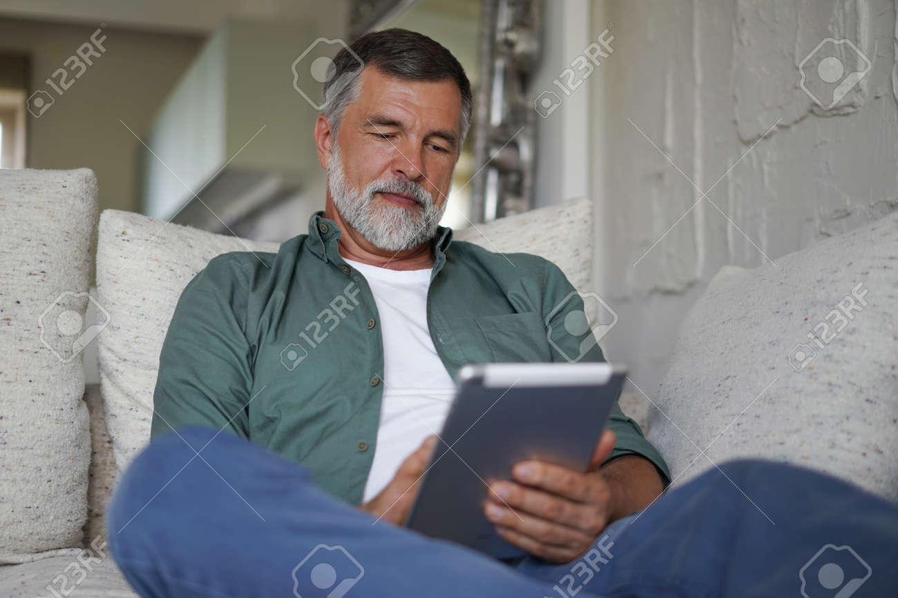 Mature handsome man websurfing on tablet at home. - 171566997