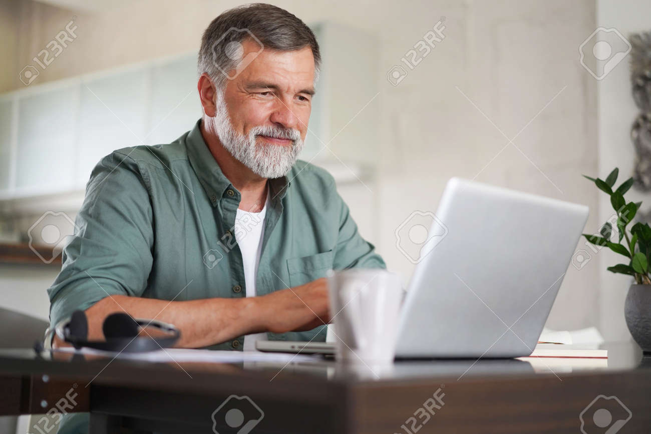 Handsome mature man in casual suit sitting at the table in home office and working at laptop - 171571085