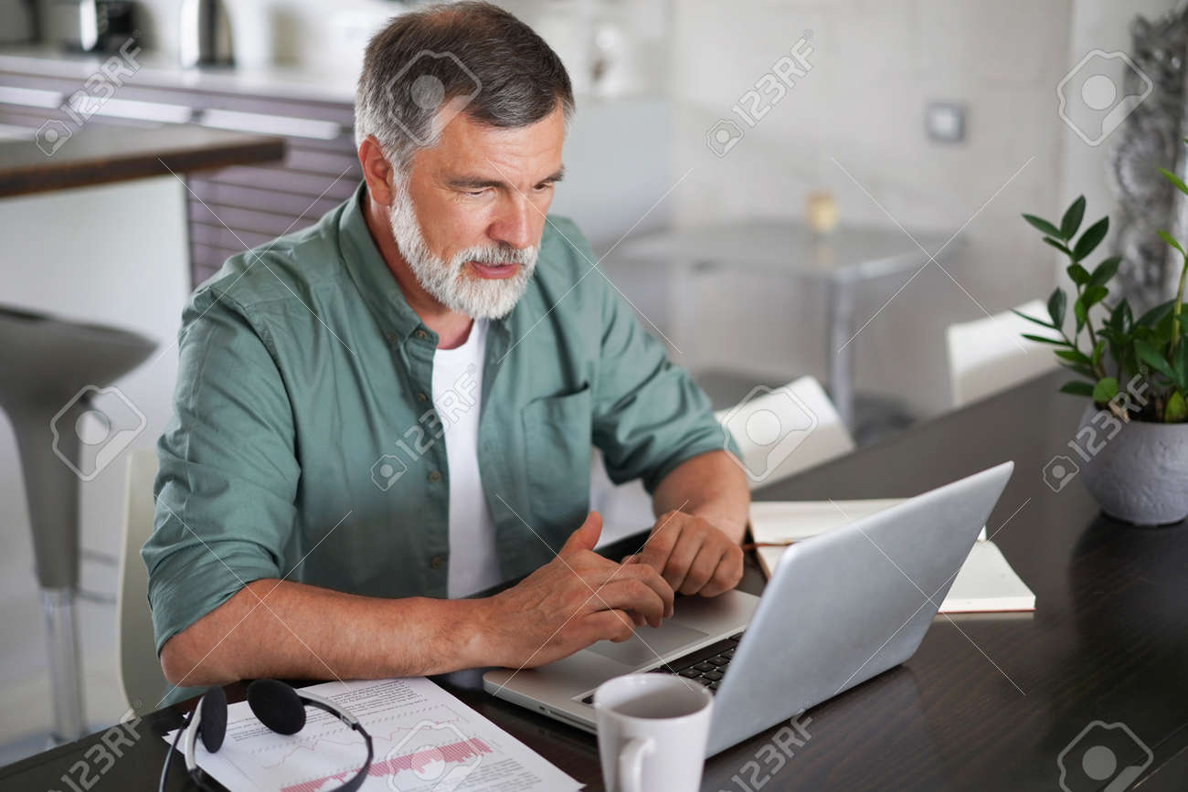 Handsome mature man in casual suit sitting at the table in home office and working at laptop - 171571087
