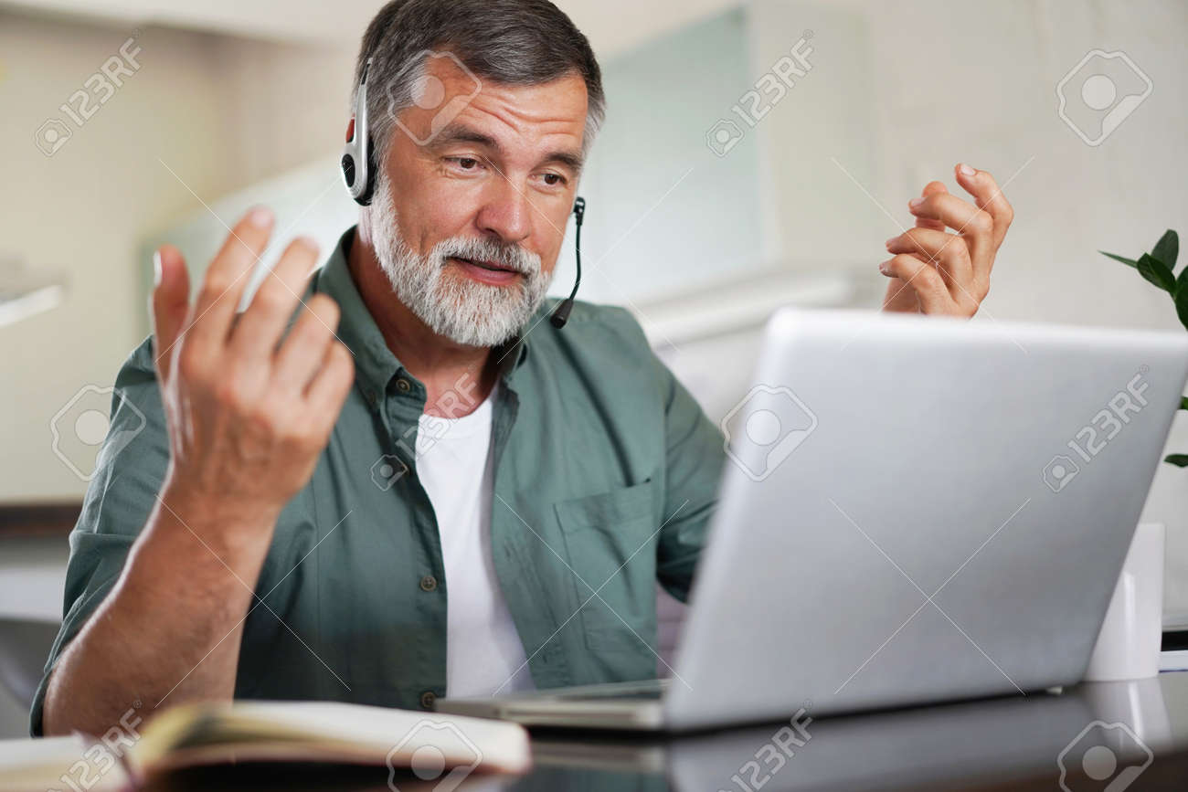 Attractive mature male remote working from home and having work confrence video call. - 171571091