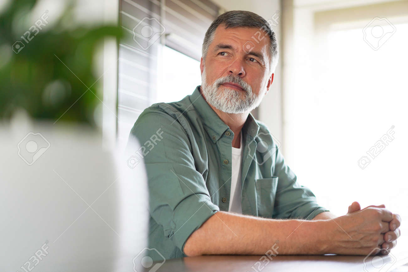 Happy attractive mature man sitting at table in kitchen. - 171571098