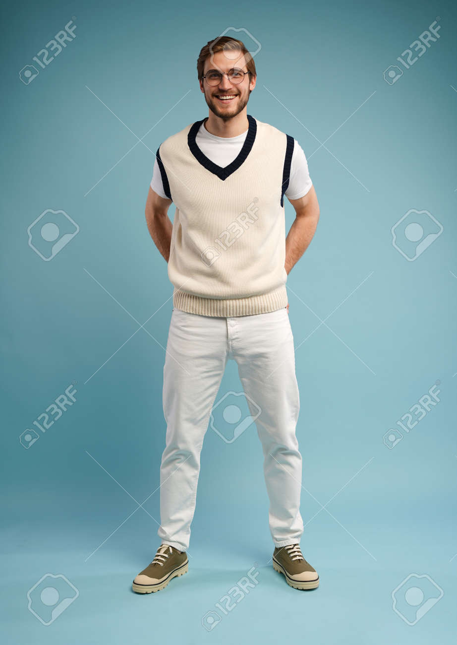 Full length of cheerful charming cute handsome man posing in front of camera isolated over blue color background - 171574569