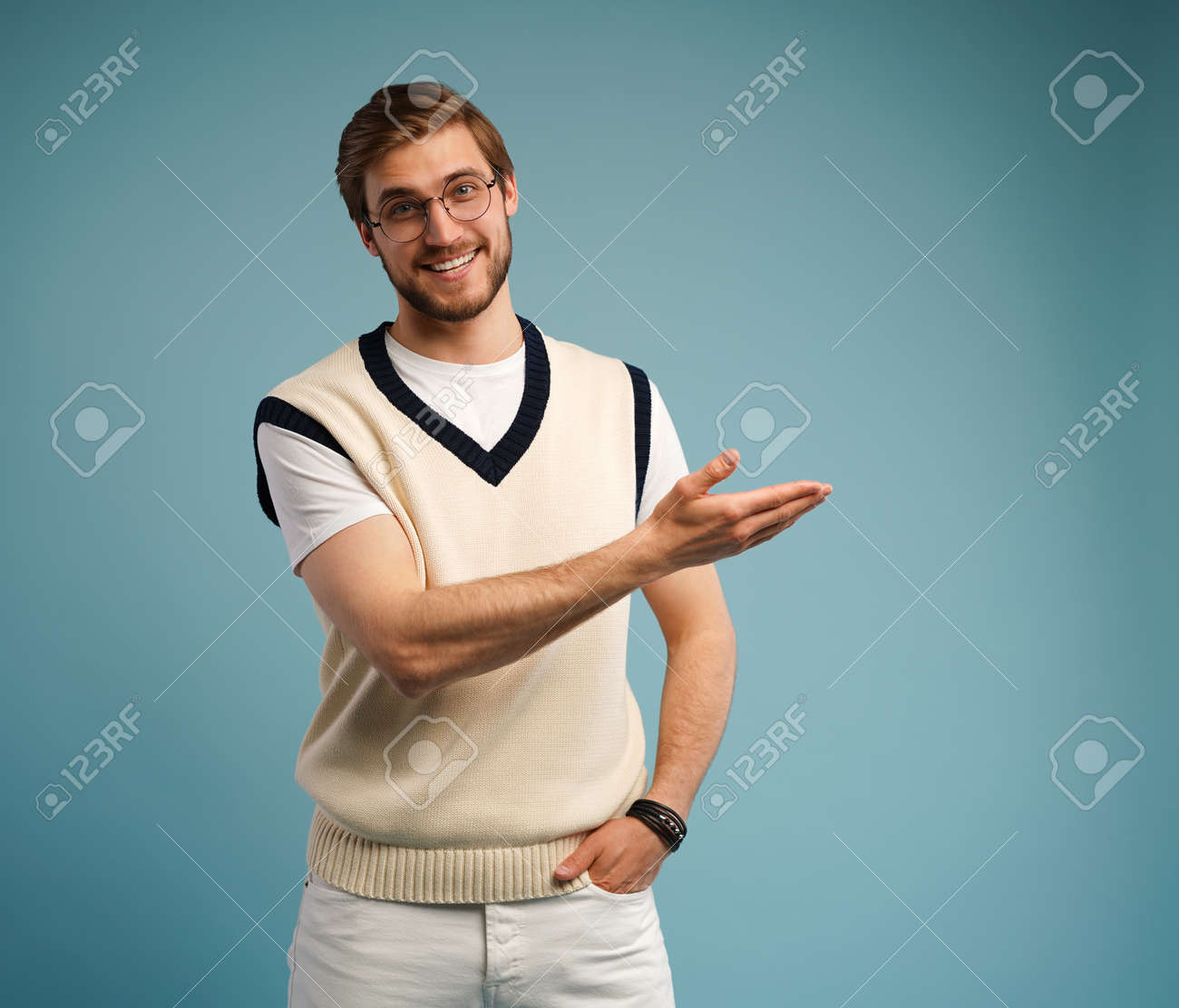 Portrait of a happy young man in casual pointing fingers away at copy space isolated over blue background. - 171574349
