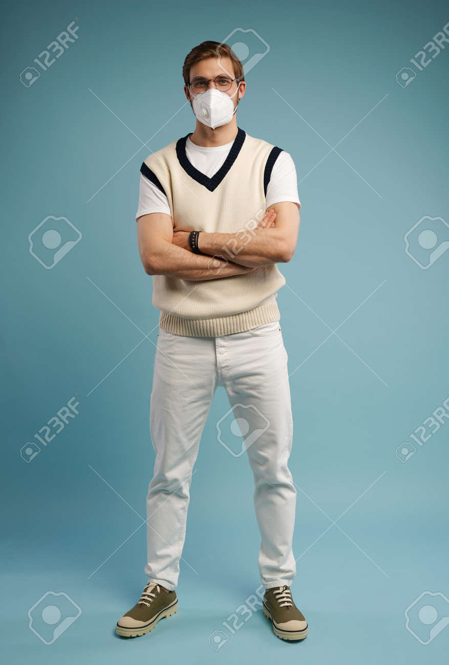 Portrait of handsome young man with surgical medical mask in casual style shirt standing, looking at camera with smile - 171597158
