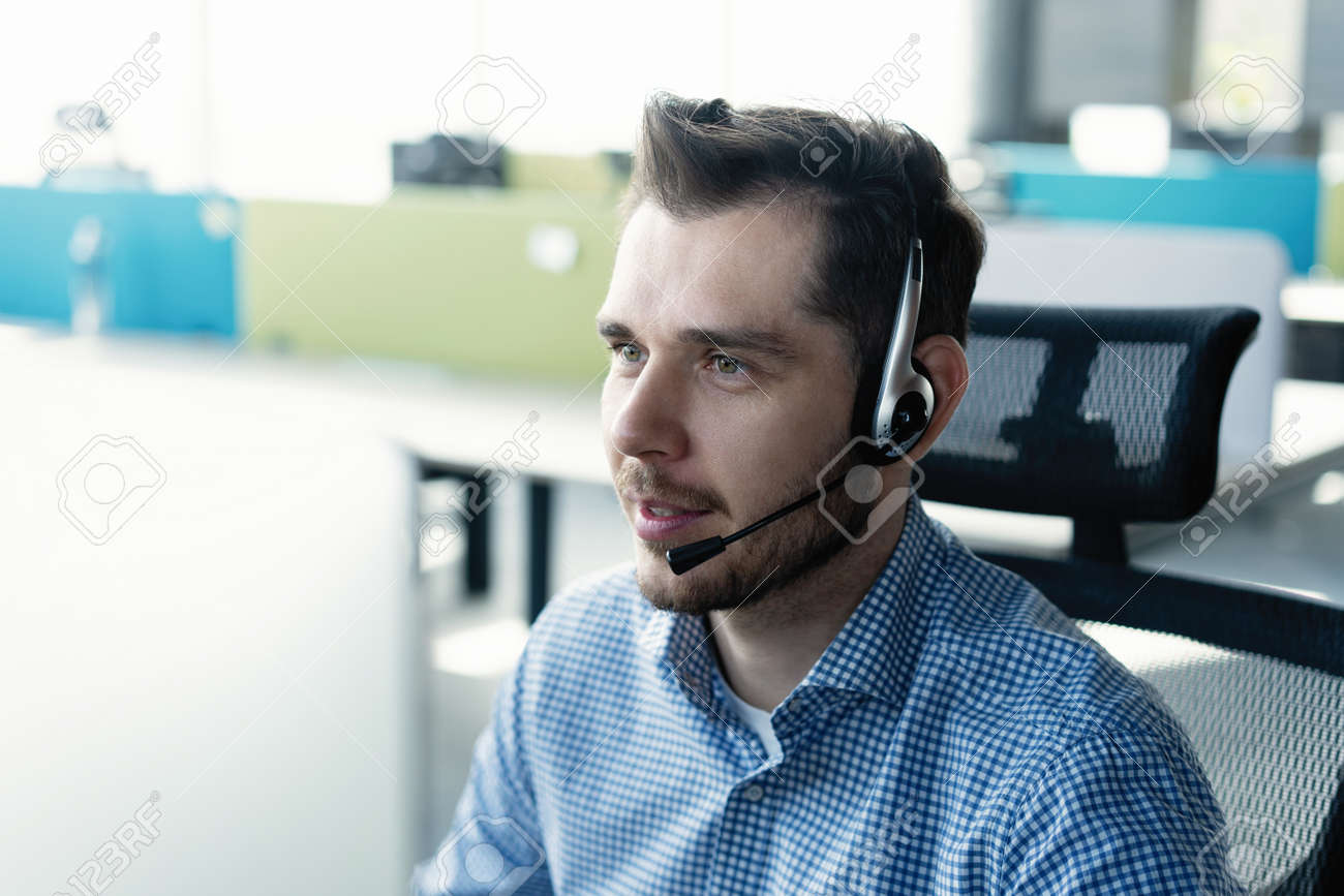 Young handsome male customer support phone operator with headset working in call center - 171798049
