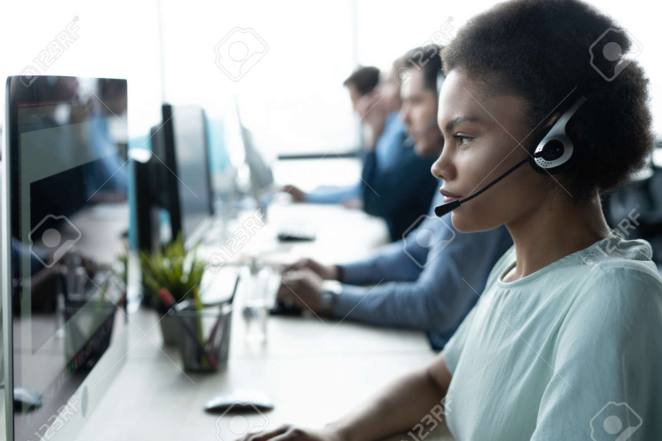 How can I help you? Beautiful call center workers in headphones are working at modern office - 171827281