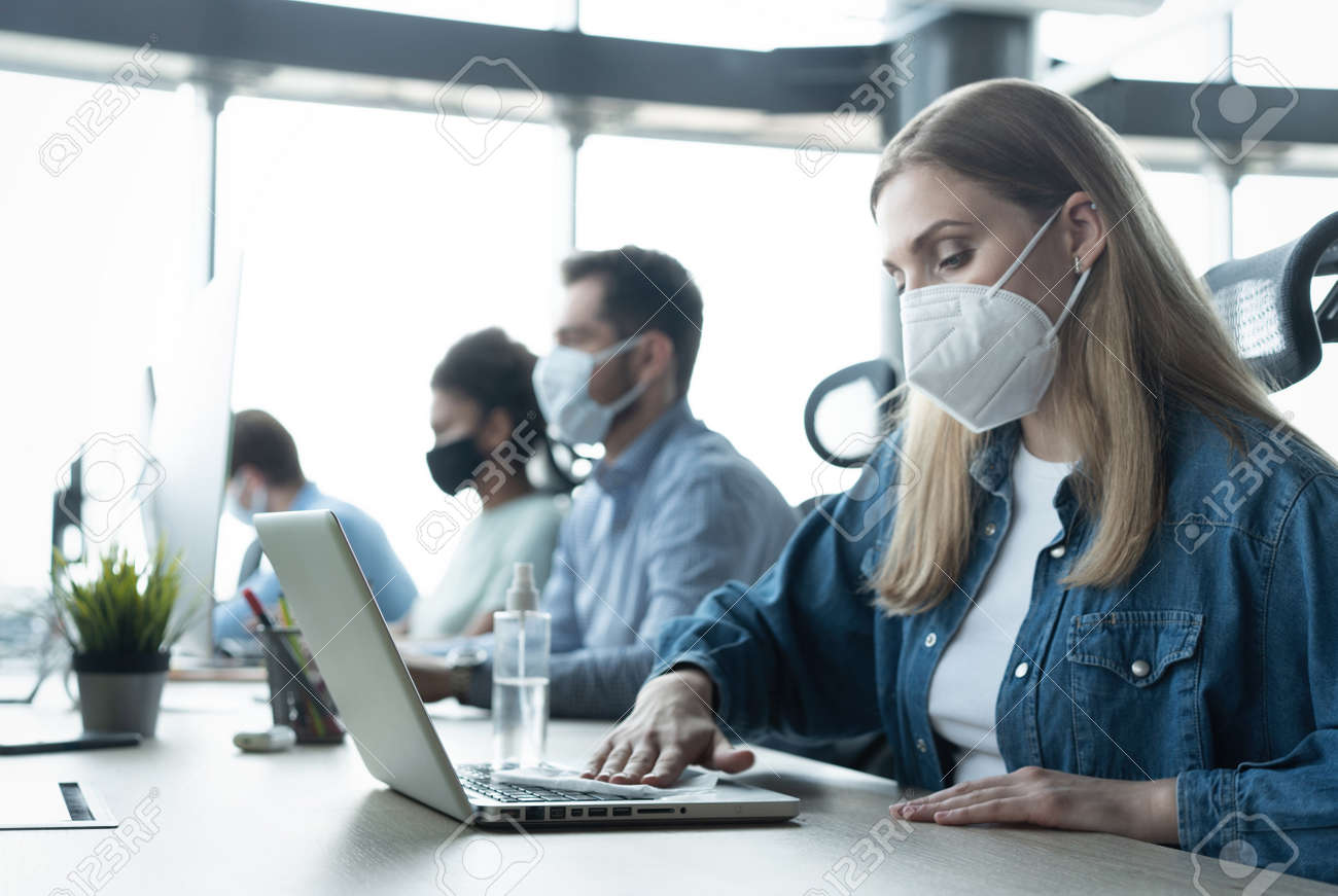 Portrait of young businesspeople with face masks working indoors in office, disinfecting laptop - 171828515