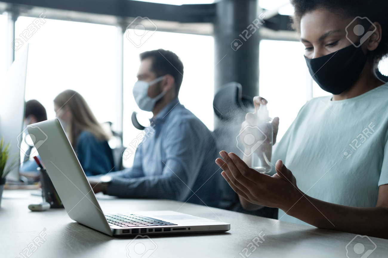 Portrait of young businesspeople with face masks working indoors in office, disinfecting laptop - 171828395