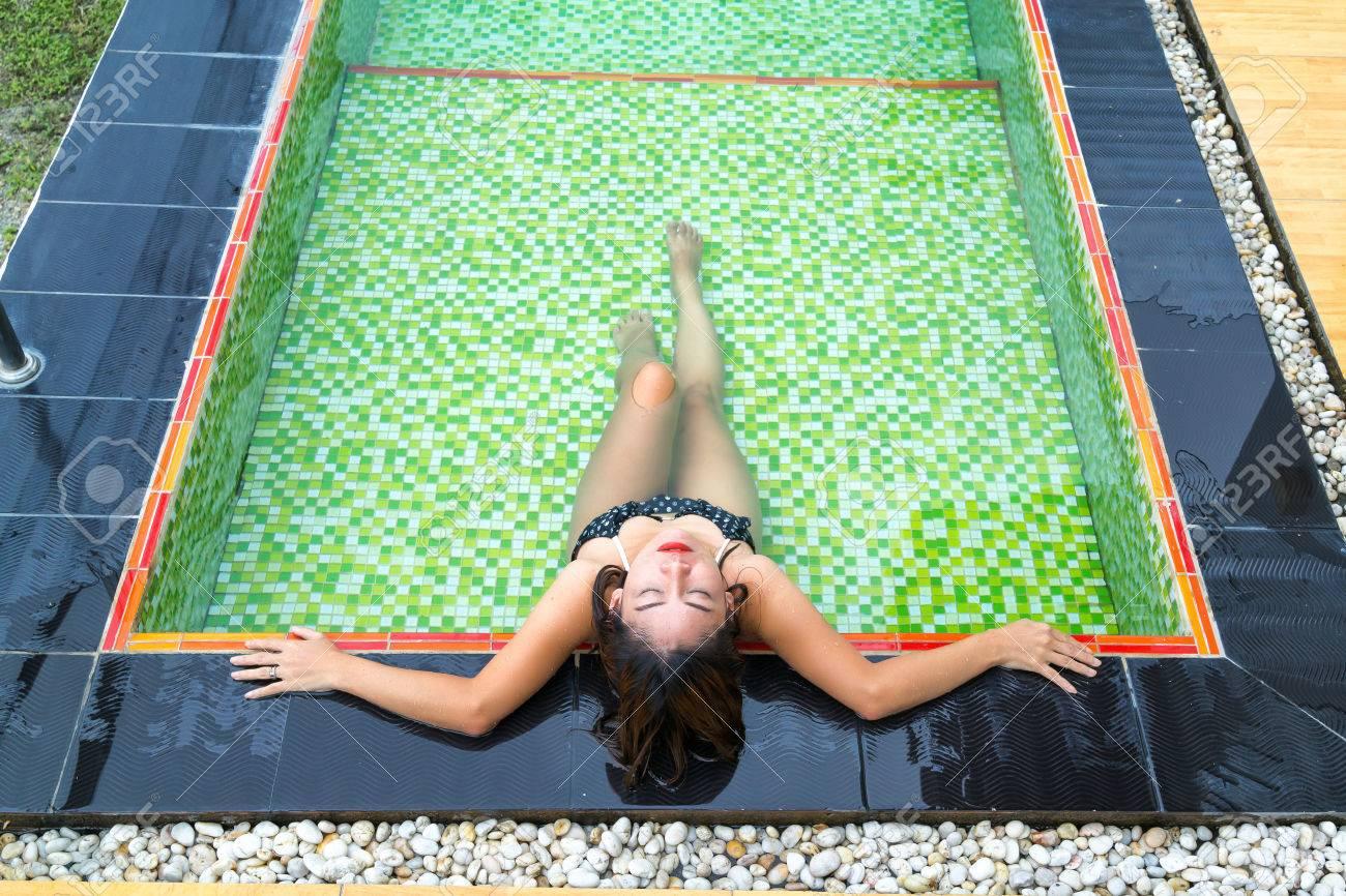 Aziatisch meisje in zwarte bikini liggend in het zwembad met