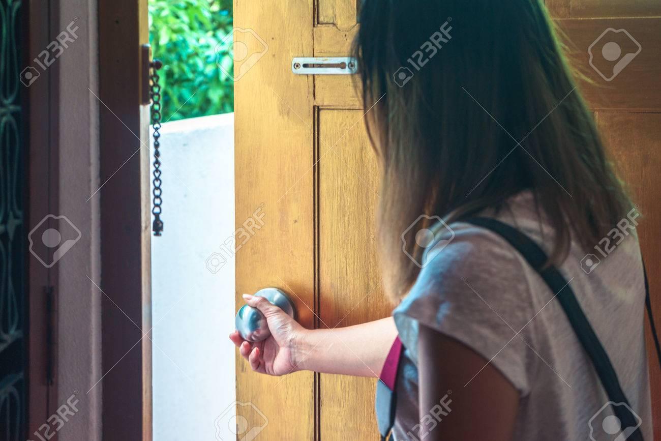 Asian woman grabbing door knob opening brown wooden door. - 63844886