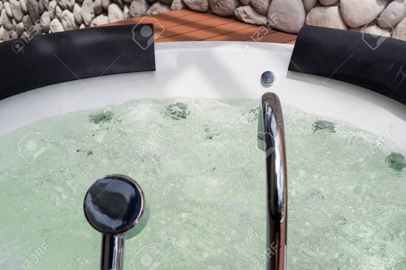 White Whirlpool Bathtub With Water Bubbles And Steel Faucet And ...