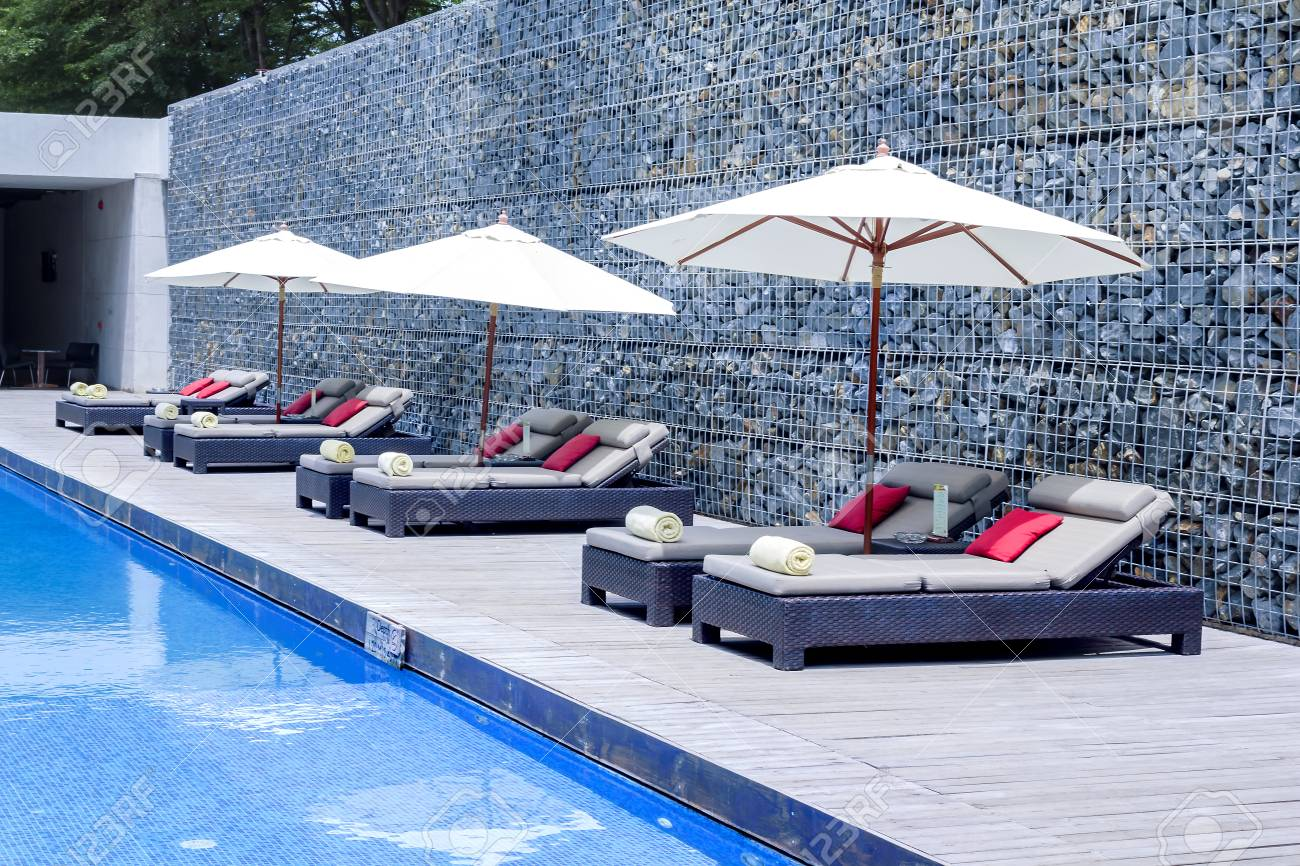 Relax Beach chairs and Umbrella at Swimming Pool Side.